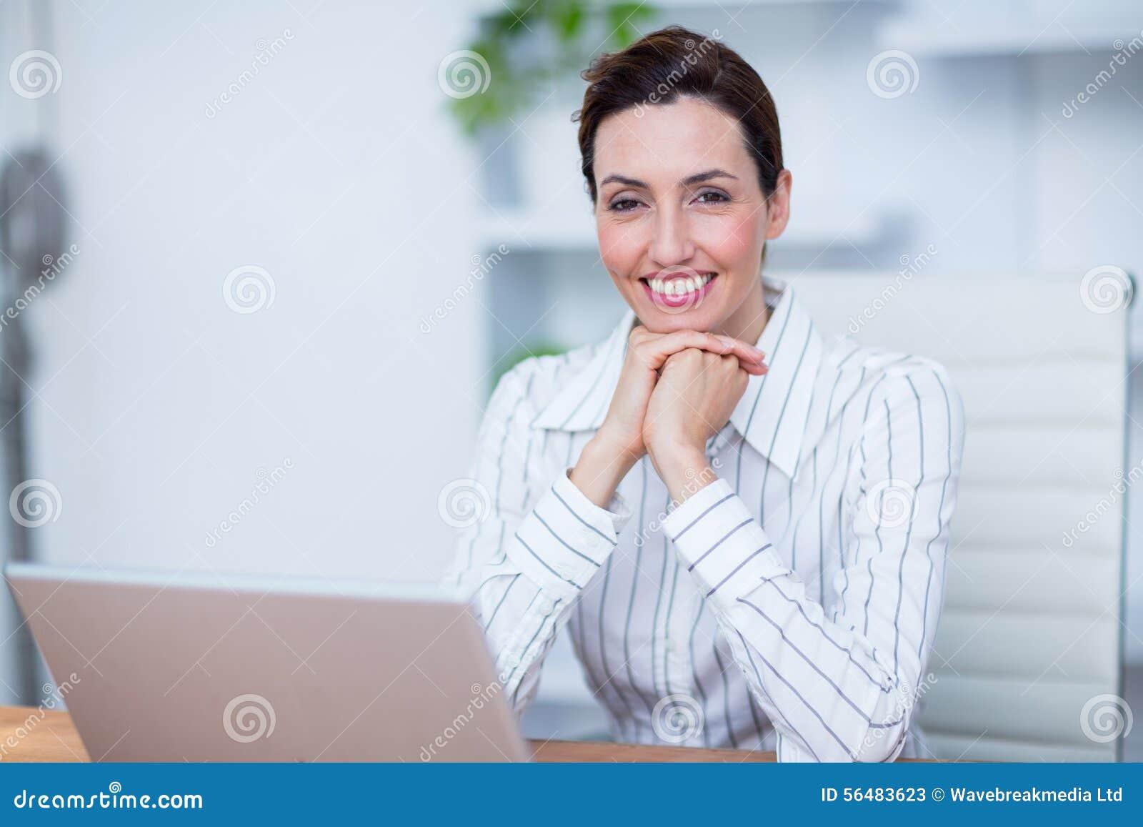 Femme d affaires de sourire de jolie brune à l aide de l ordinateur portable