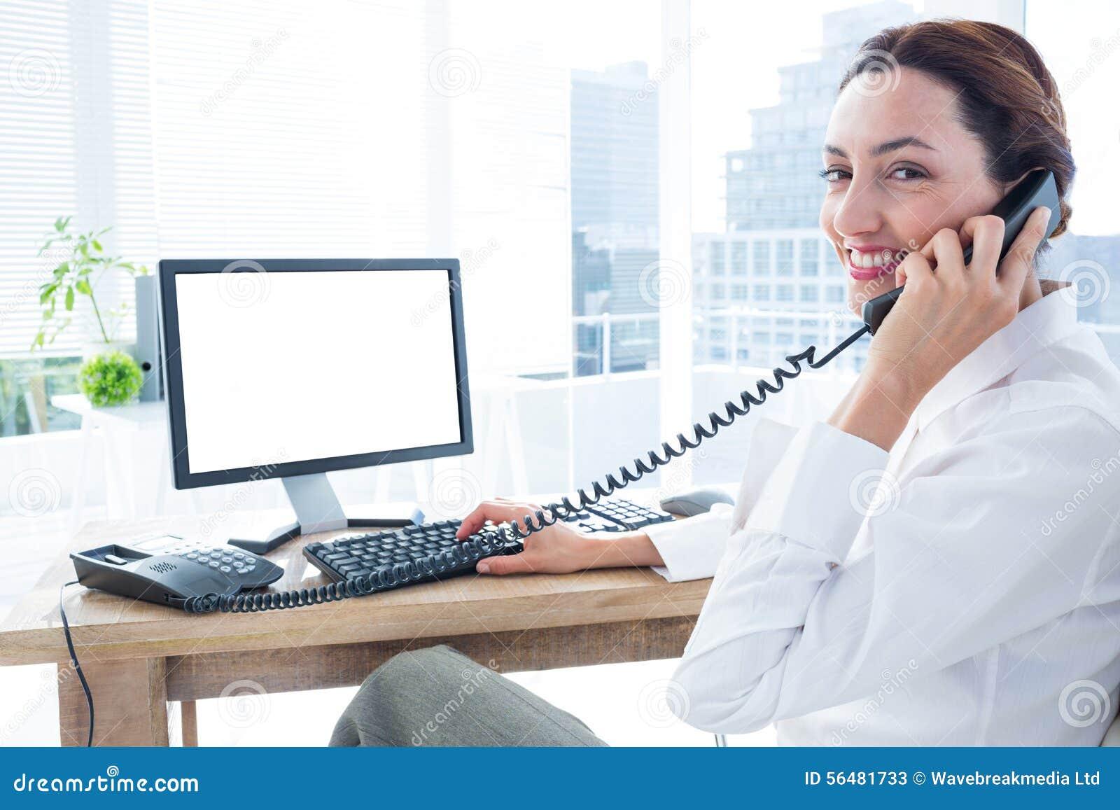 Femme d affaires de sourire employant l ordinateur et téléphoner
