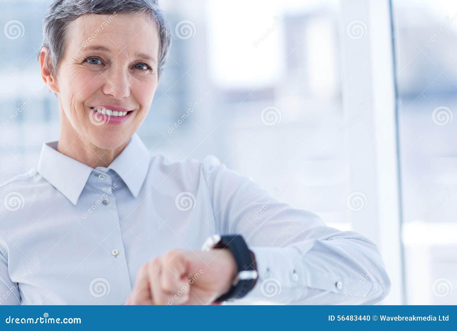 Femme d affaires de sourire employant son smartwatch