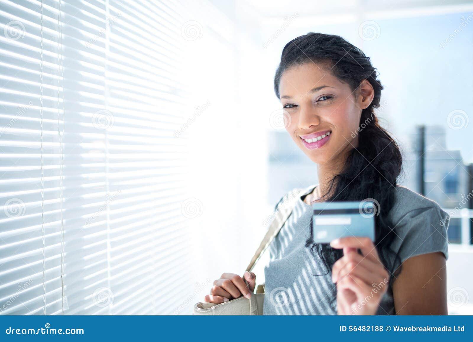 Femme d affaires de sourire regardant l appareil-photo avec la carte de crédit