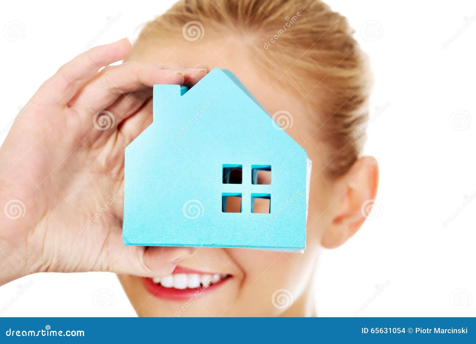 Femme d affaires de sourire regardant par une fenêtre de papier de maison