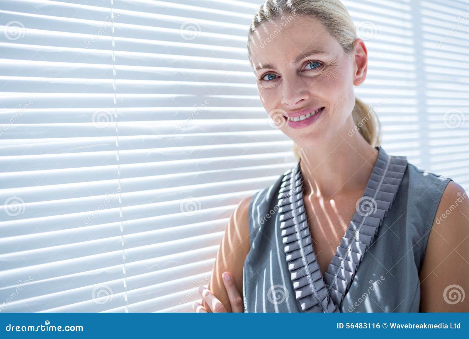 Femme d affaires de sourire se tenant dans le bureau