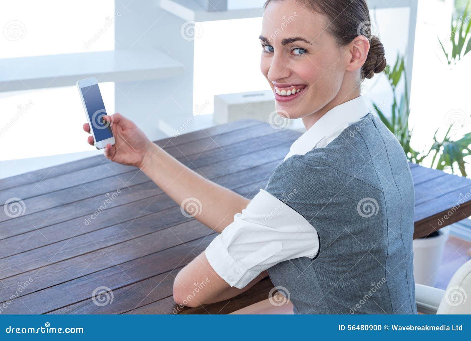 Femme d affaires heureuse à l aide de son smartphone