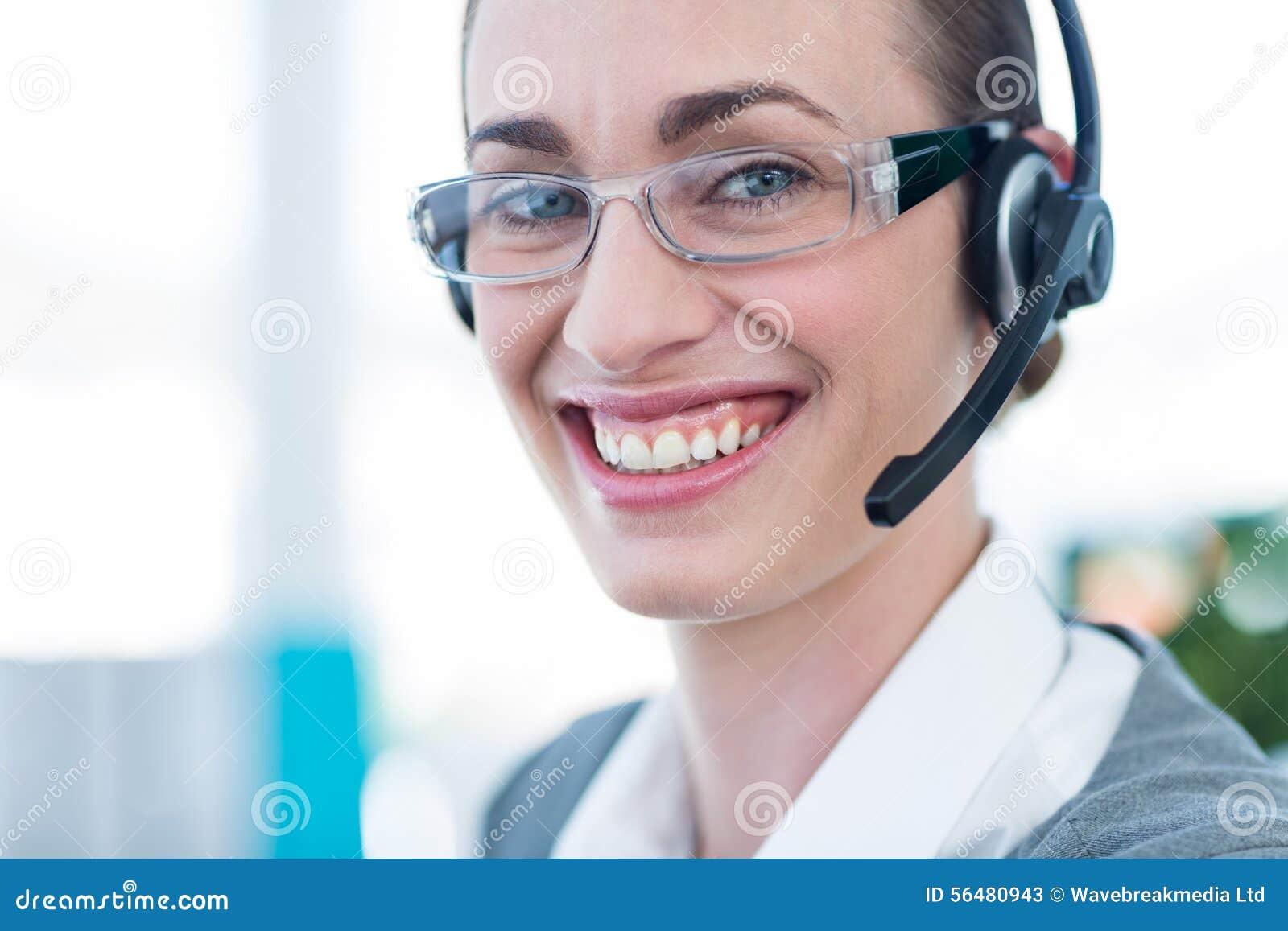Femme d affaires heureuse regardant l appareil-photo avec le casque