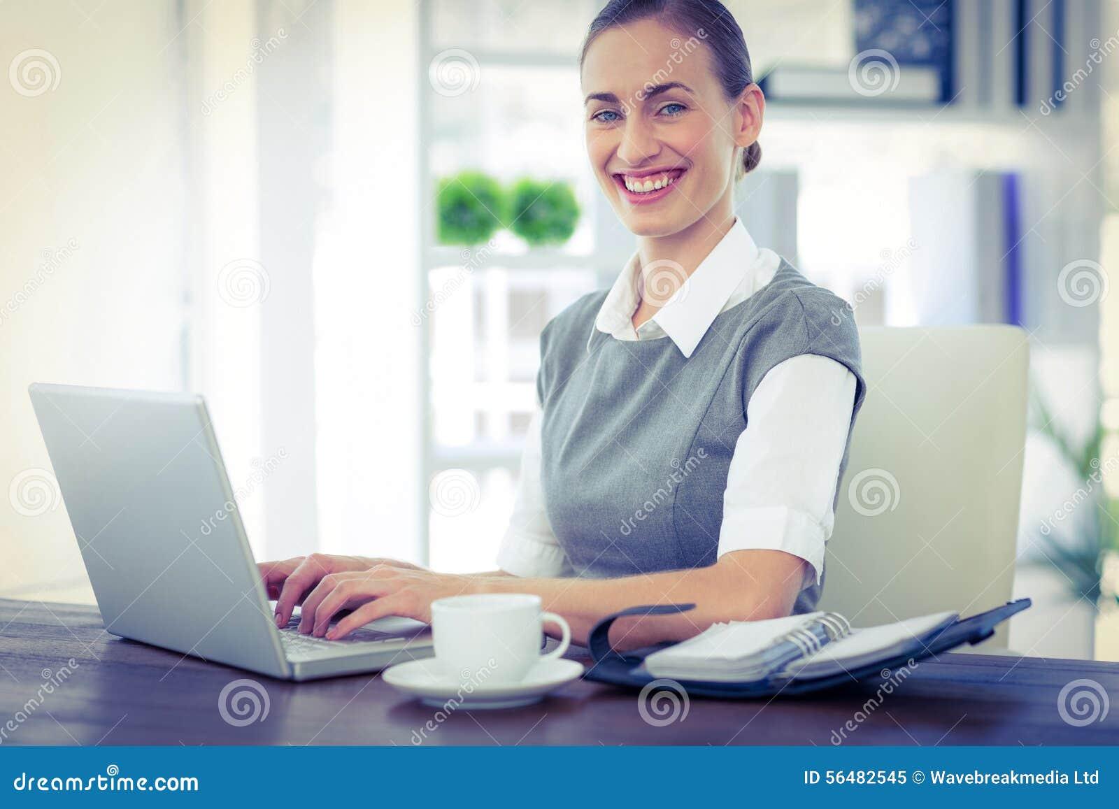 Femme d affaires heureuse travaillant sur l ordinateur portable et regardant l appareil-photo