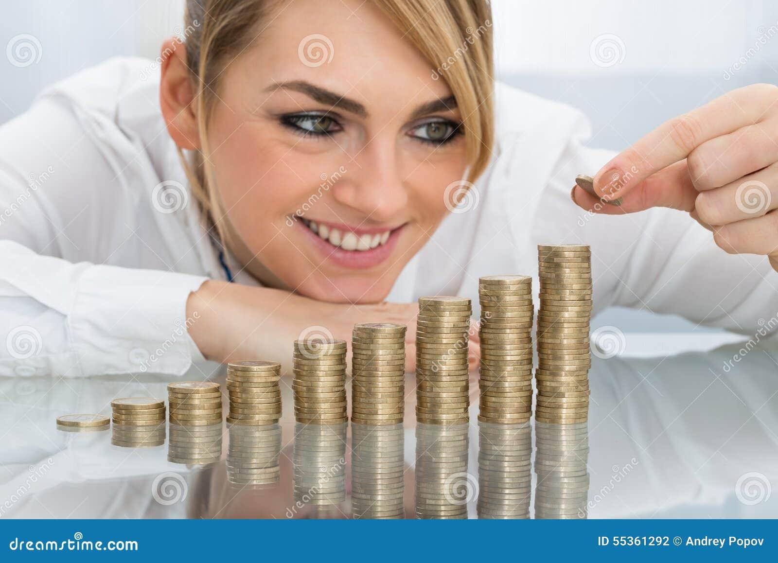 Femme d affaires mettant la pièce de monnaie sur la pile de pièces de monnaie