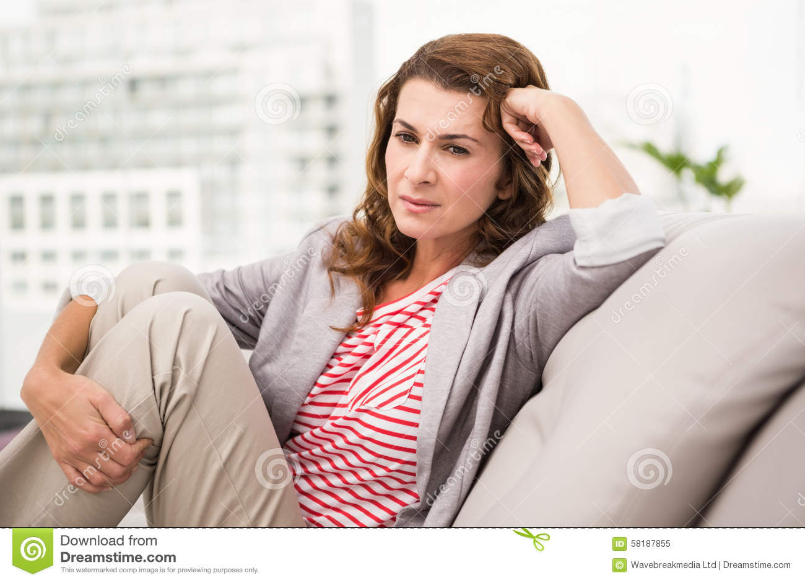 Femme d affaires occasionnelle inquiétée s asseyant sur le divan