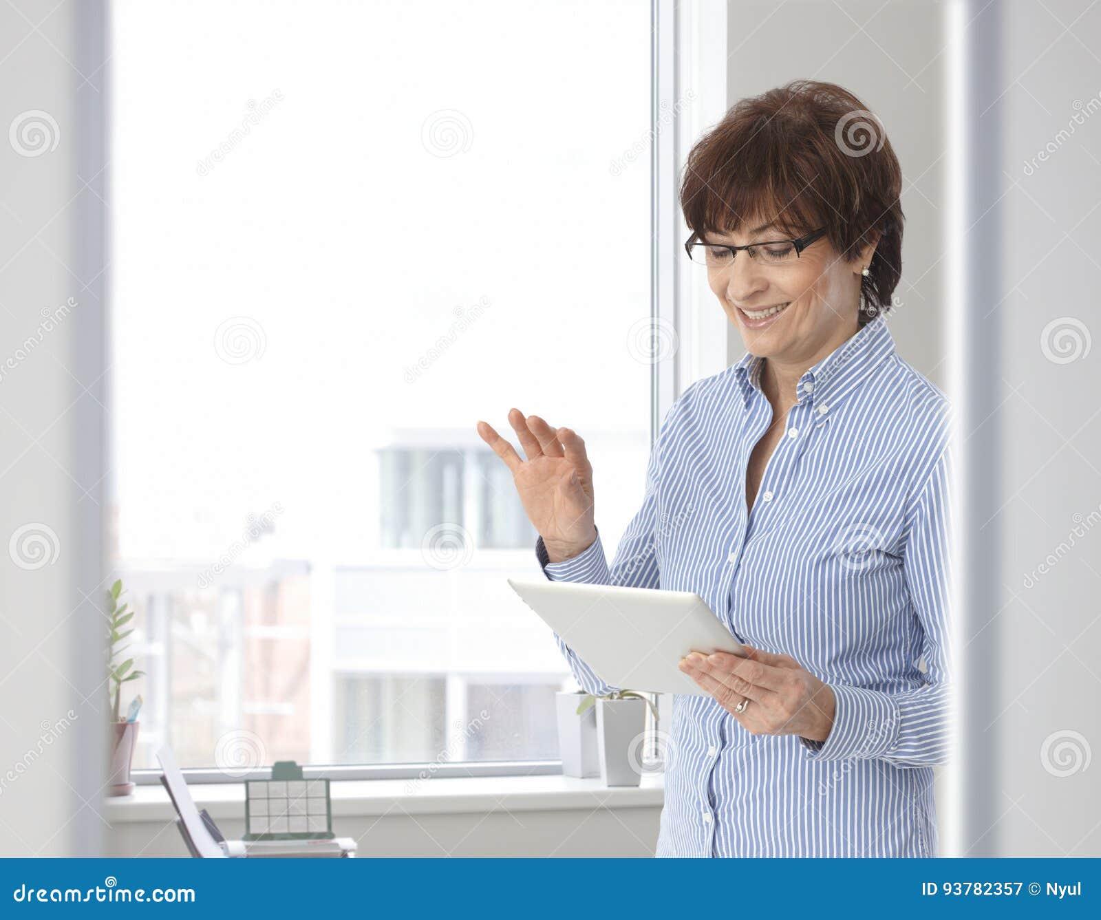 Femme d affaires occasionnelle supérieure avec la tablette
