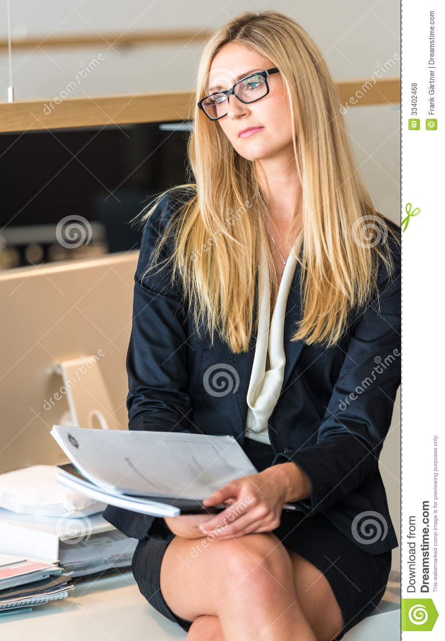 femme d 39 affaires in office working sur un document photo stock image du robe regarder 33402468. Black Bedroom Furniture Sets. Home Design Ideas