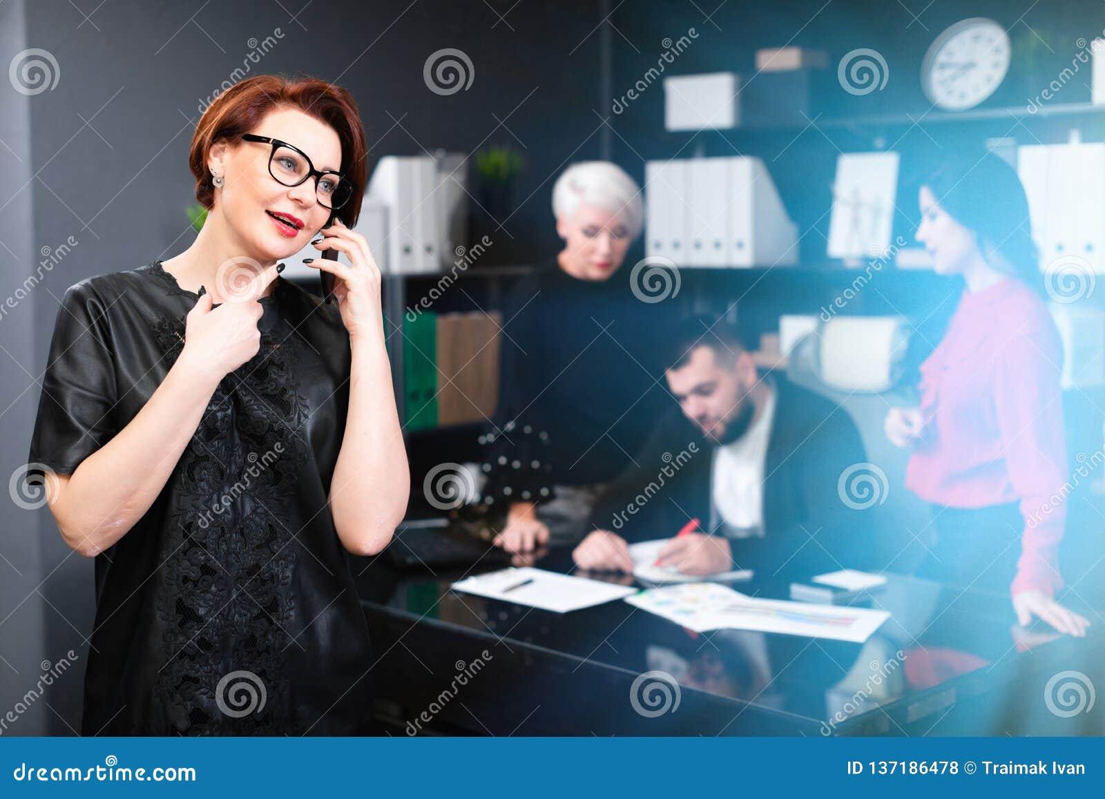 Femme d affaires parlant au téléphone sur le fond des employés de bureau discutant le projet