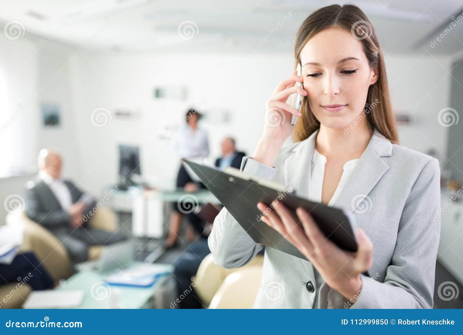 Femme d affaires Reading Clipboard While employant Smartphone dans le bureau
