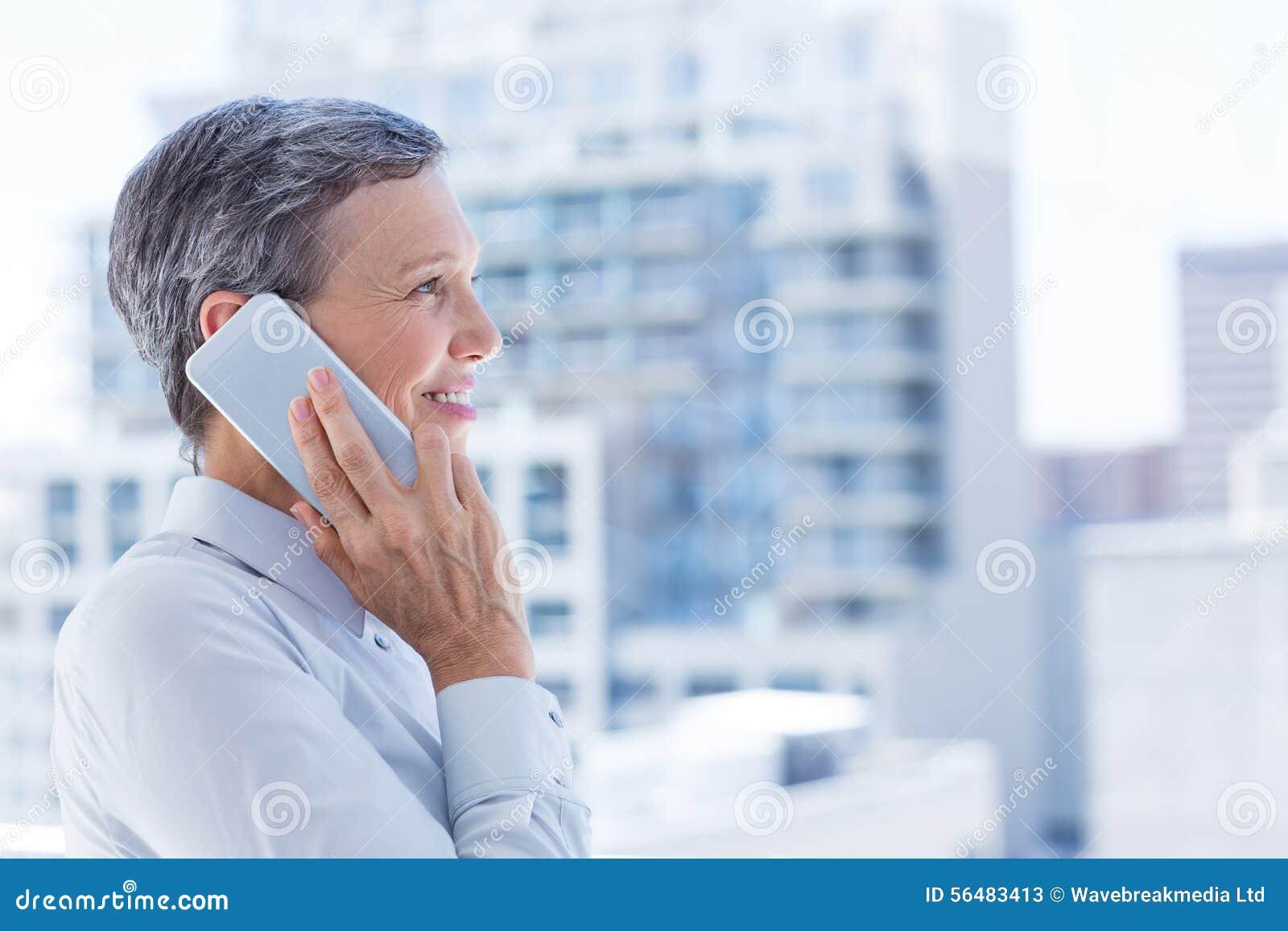 Femme d affaires regardant par la fenêtre tandis qu au téléphone