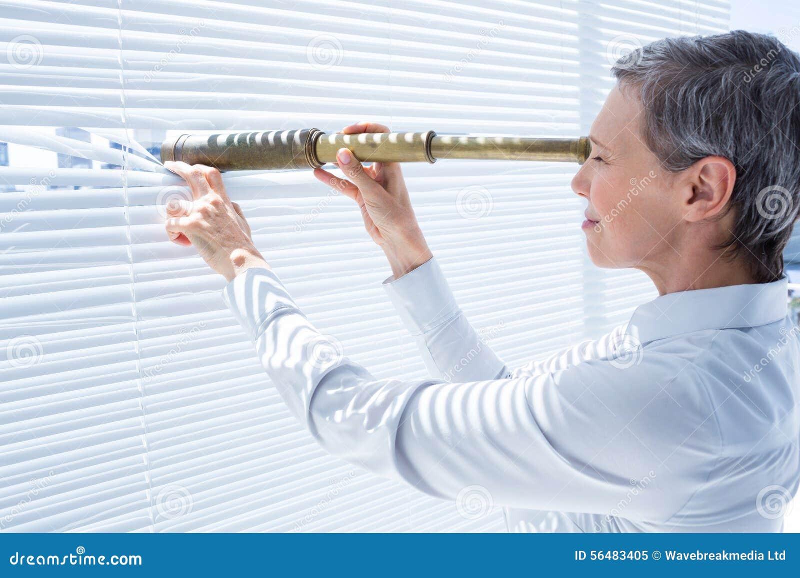 Femme d affaires regardant par le champ-verre dans le bureau