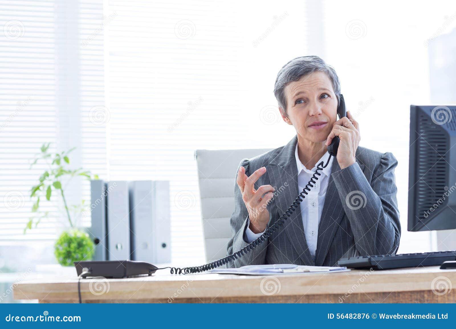 Femme d affaires sérieuse téléphonant et à l aide de l ordinateur