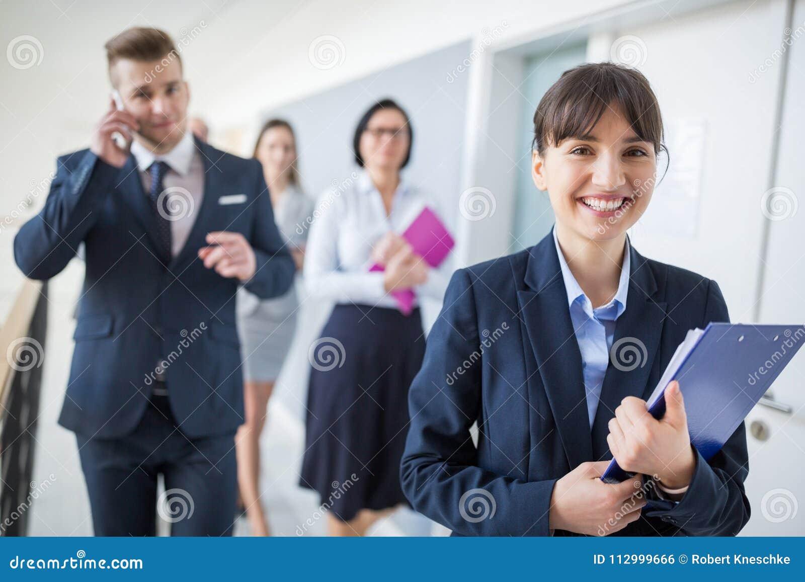 Femme d affaires sûre Smiling While Walking avec l équipe