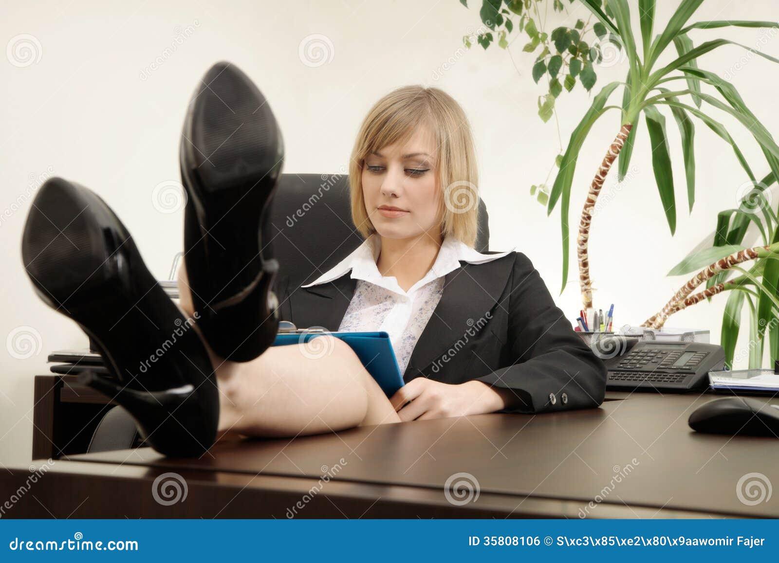 Femme d affaires s asseyant avec des pieds sur le bureau photo