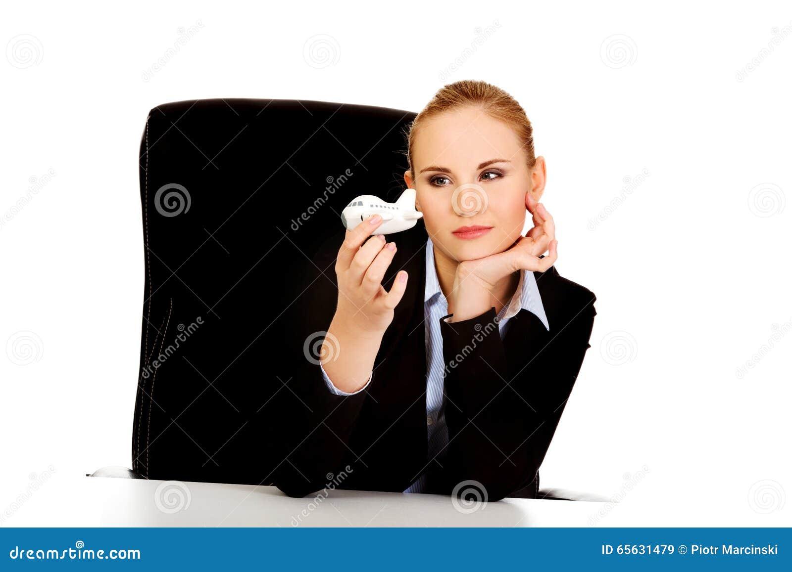 Femme d affaires s asseyant derrière le bureau et tenant un avion de jouet