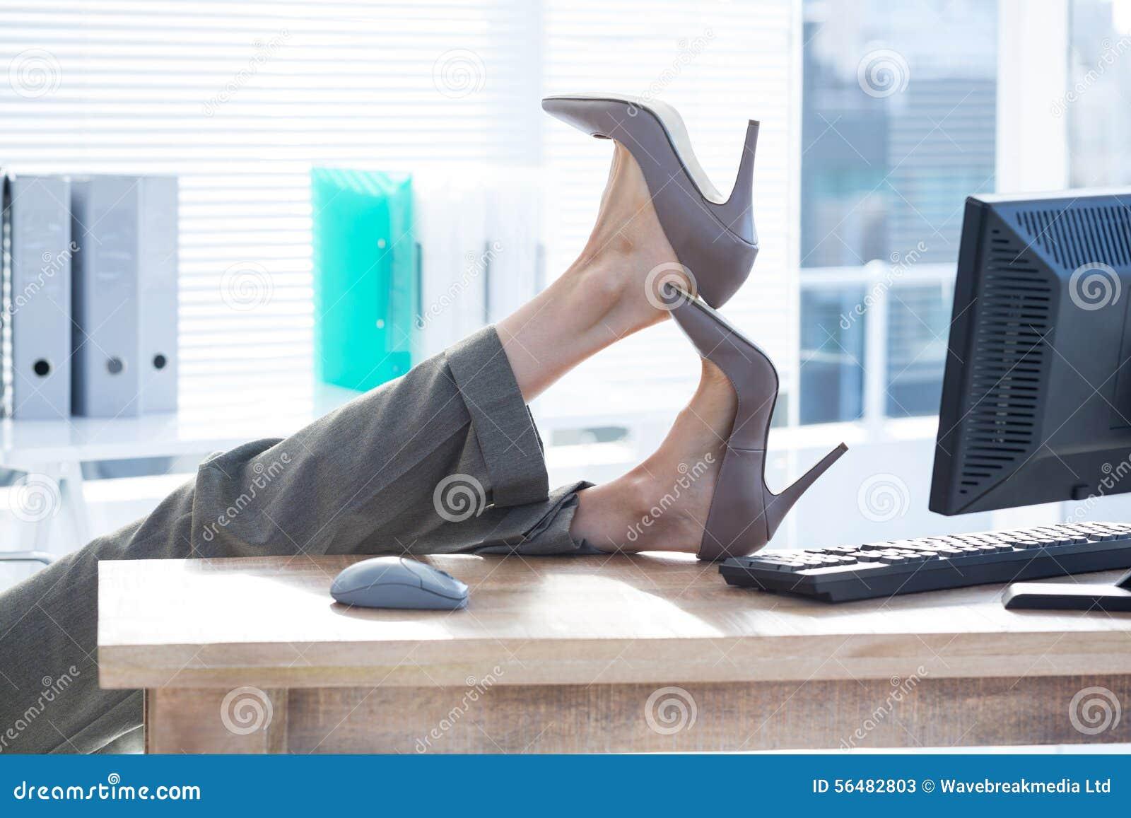 Femme d affaires s asseyant sur la chaise pivotante avec des pieds