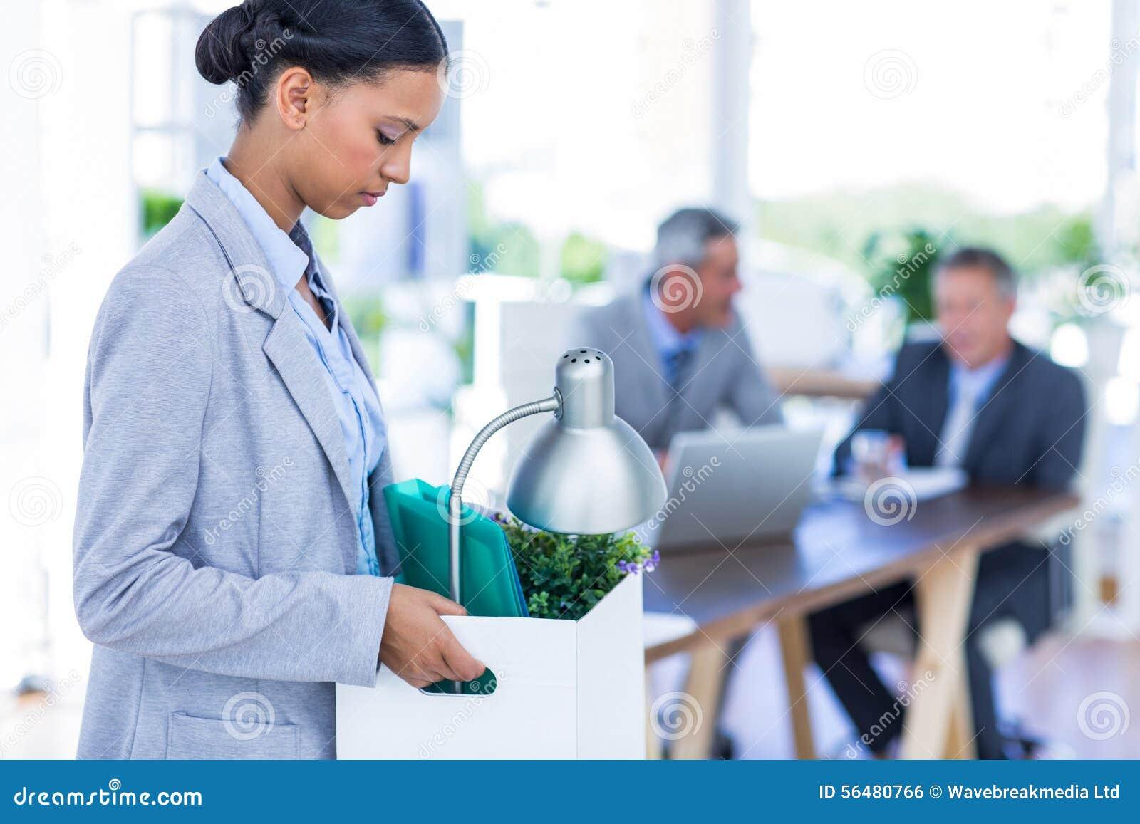Femme d affaires tenant la boîte avec ses collègues derrière elle