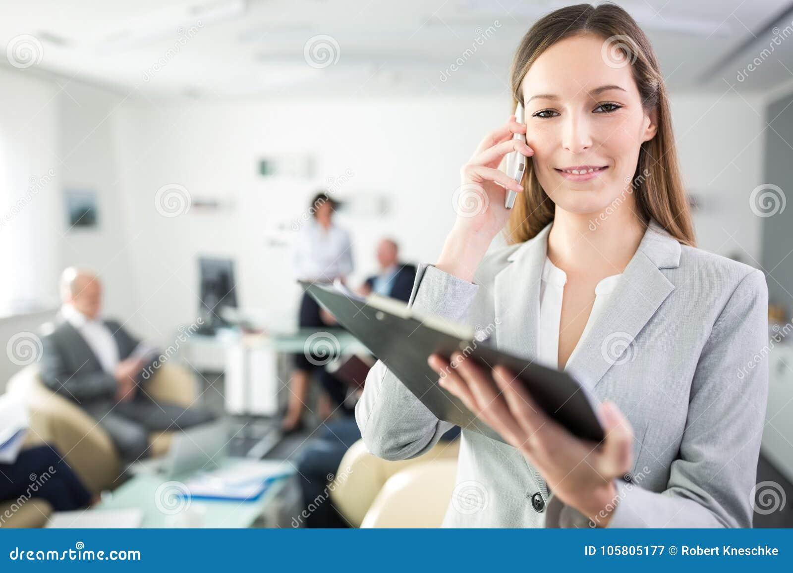Femme d affaires Using Mobile Phone tout en tenant le presse-papiers dans Offi