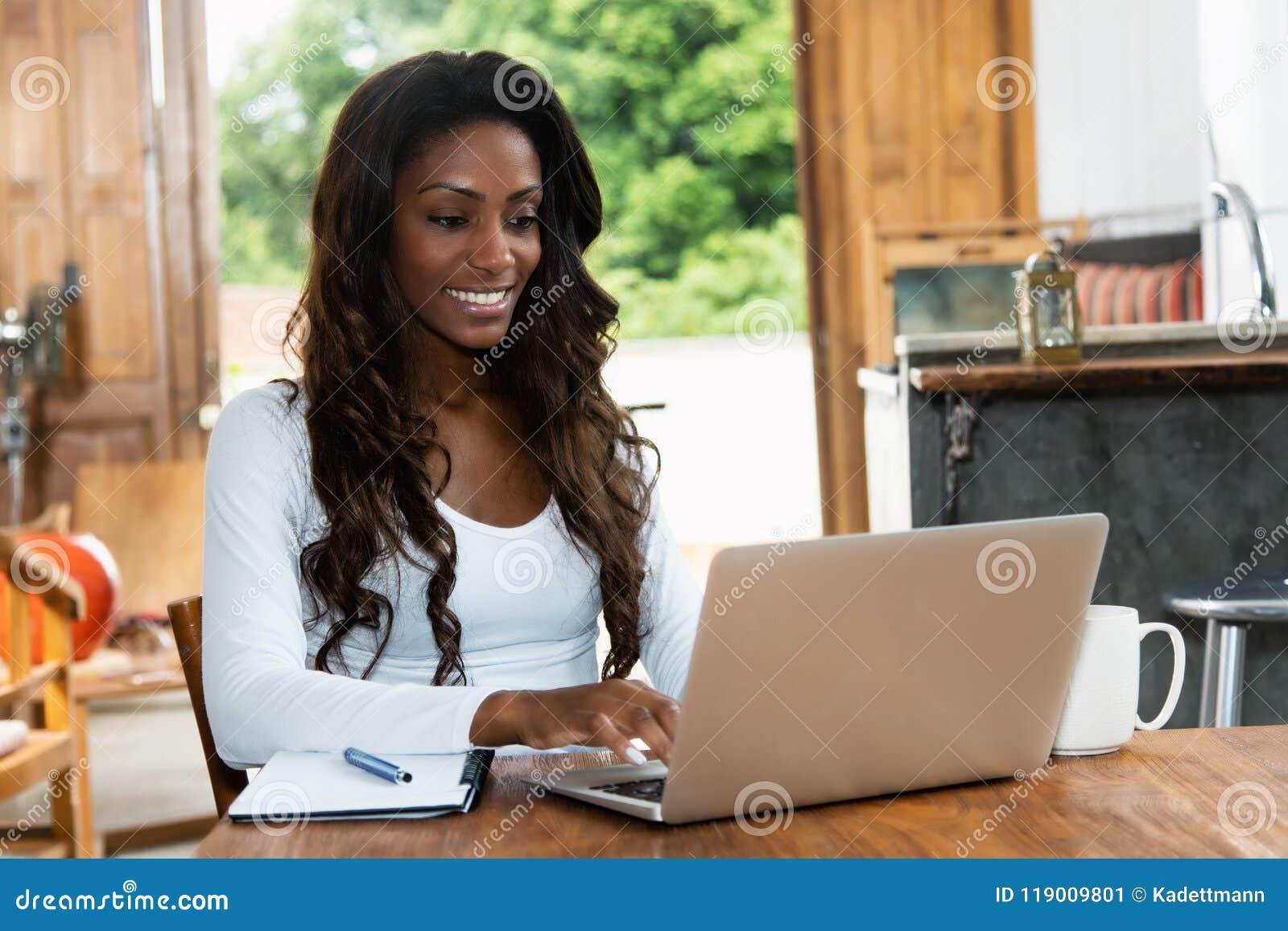 Femme d afro-américain avec de longs cheveux fonctionnant à l ordinateur