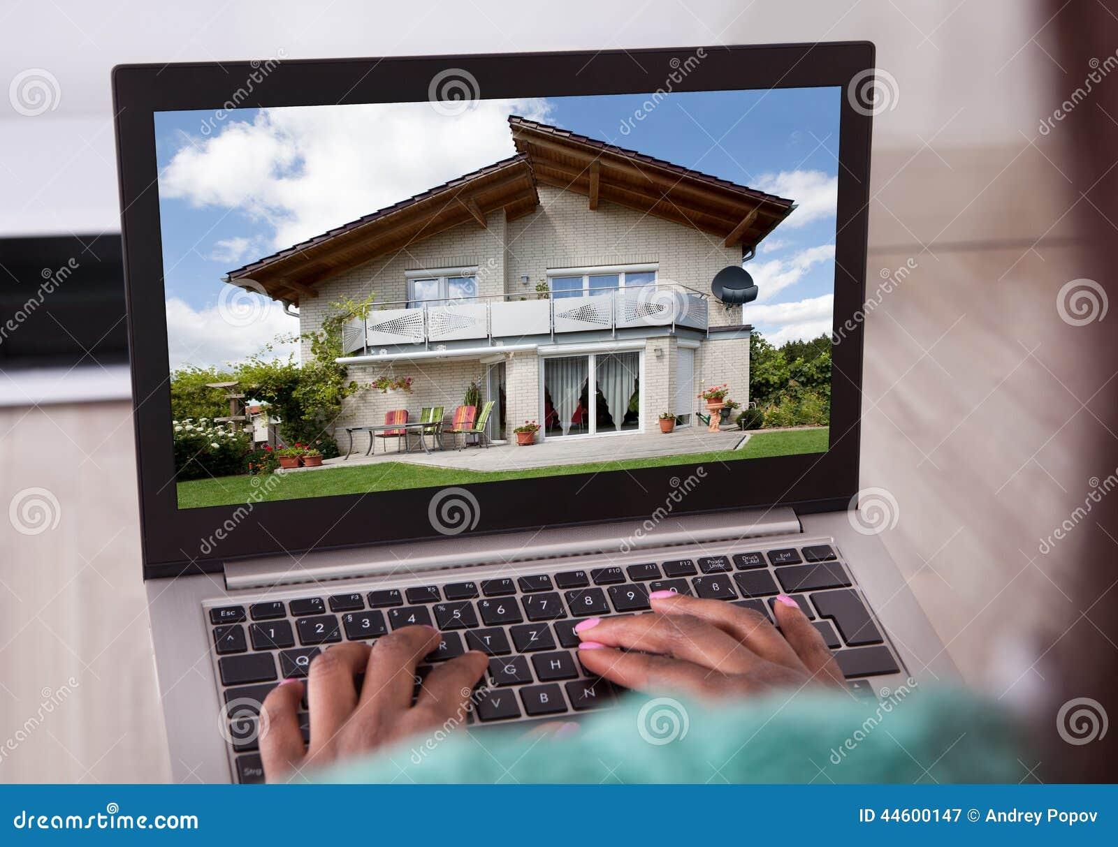 Femme d afro-américain sélectionnant la nouvelle maison sur l ordinateur portable à la maison