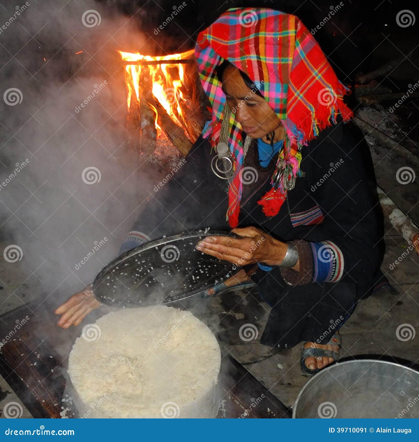 Femme d Akha faisant cuire le riz.
