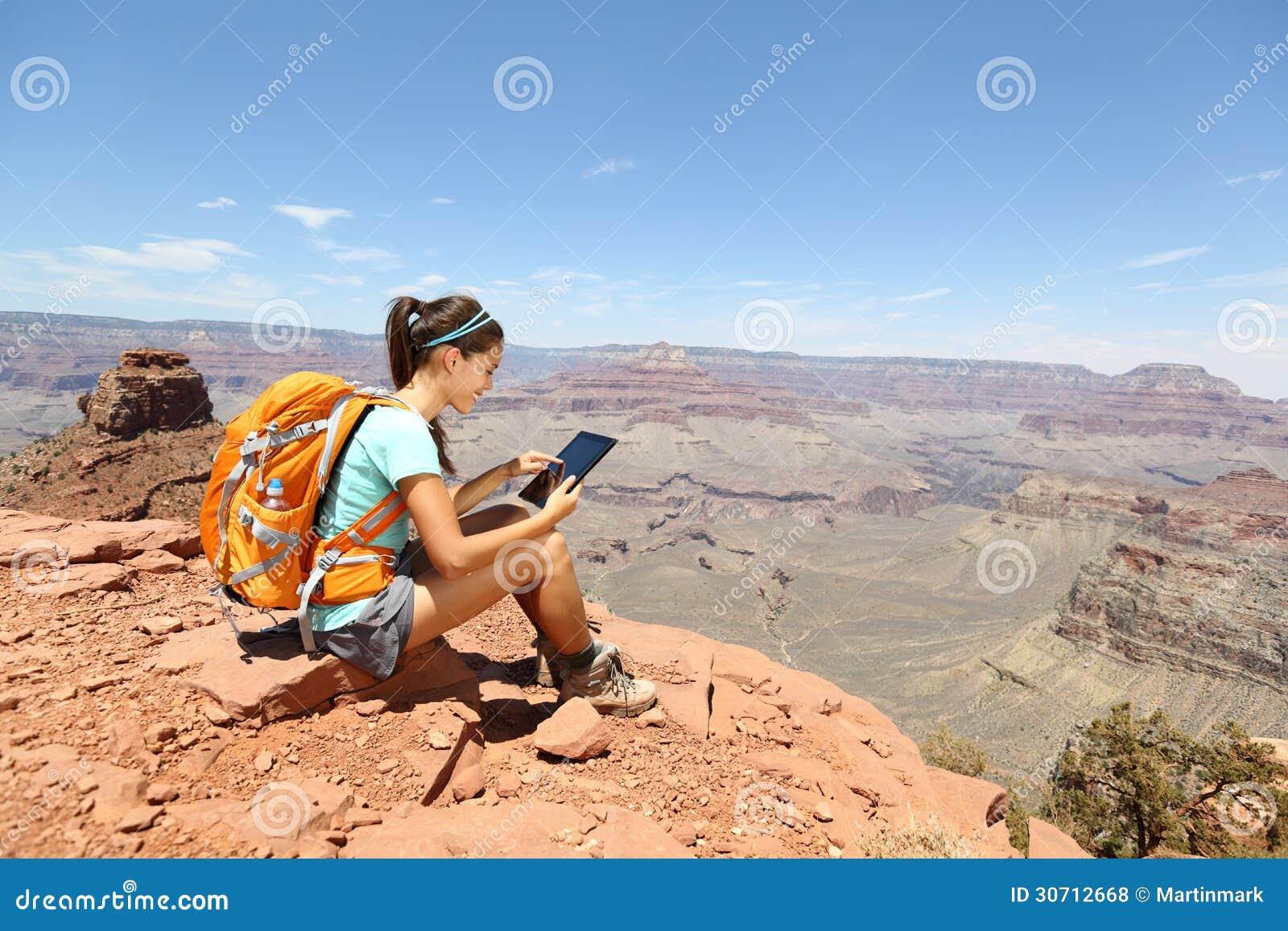 Femme d ordinateur de comprimé trimardant en canyon grand