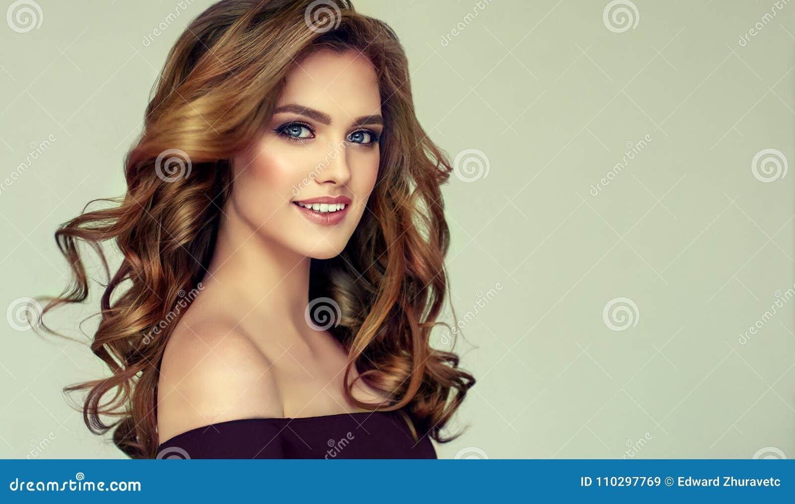 Femme d une chevelure de Brown avec la coiffure volumineuse, brillante et bouclée Cheveux crépus