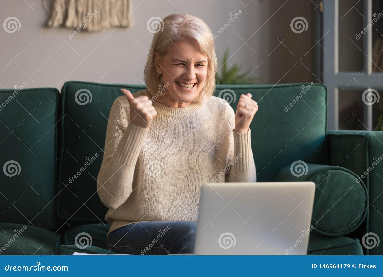 Femme d une chevelure grise enthousiaste heureuse célébrant la victoire en ligne, utilisant l ordinateur portable