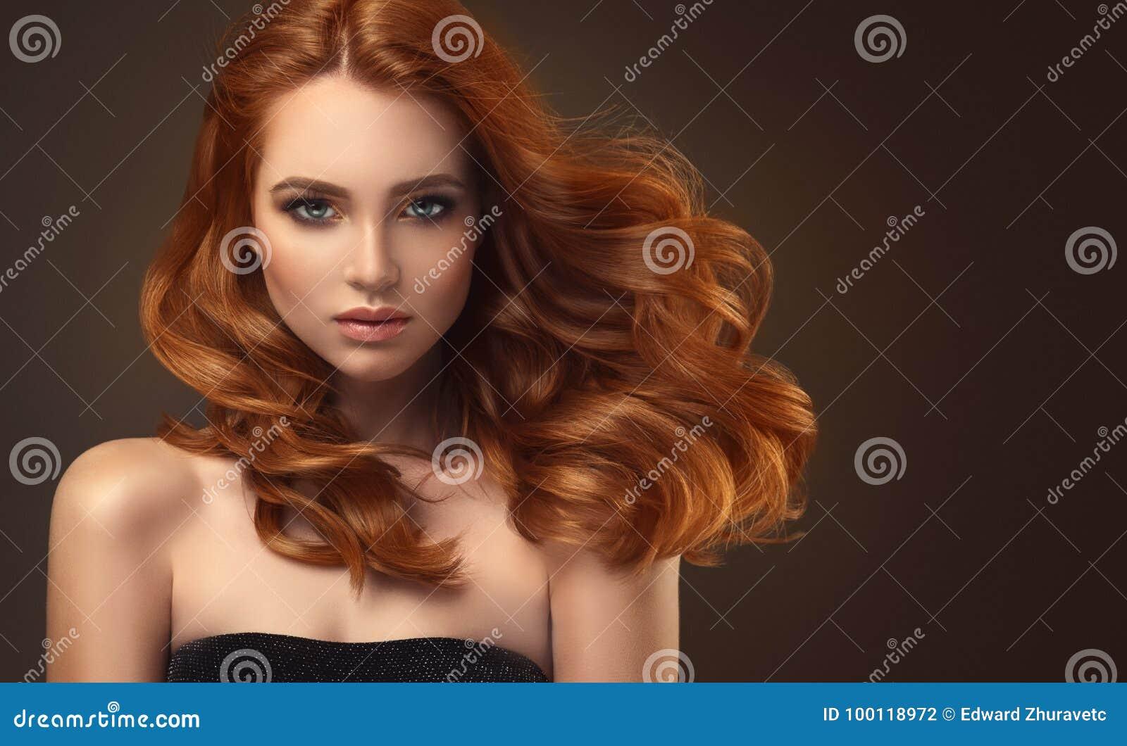 Femme d une chevelure rouge avec la coiffure volumineuse, brillante et bouclée Cheveu de vol