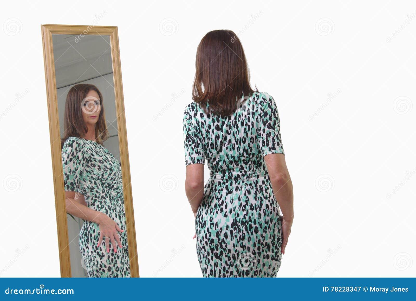 Femme d une cinquantaine d années attirante regardant la réflexion dans le miroir