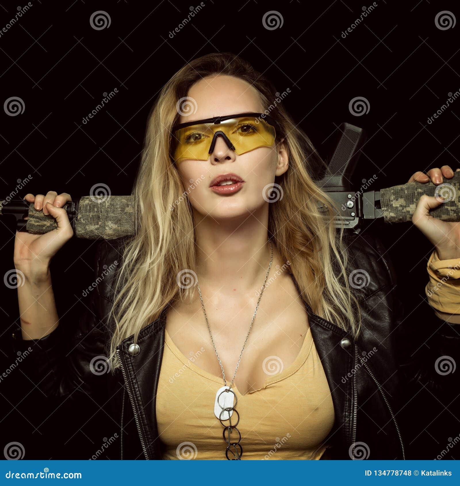 Femme dangereuse blonde sexy avec l arme automatique