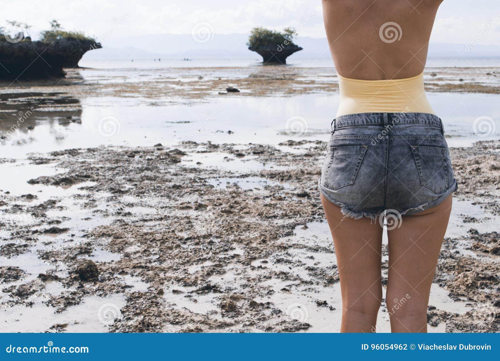 Femme dans des shorts de boho et maillot de bain sur la plage Bord de la mer et montagnes sur la marée basse