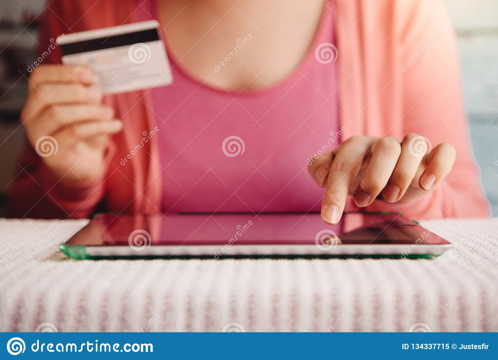 Femme dans l achat rose dans le magasin en ligne dans l Internet avec le comprimé et la carte de crédit