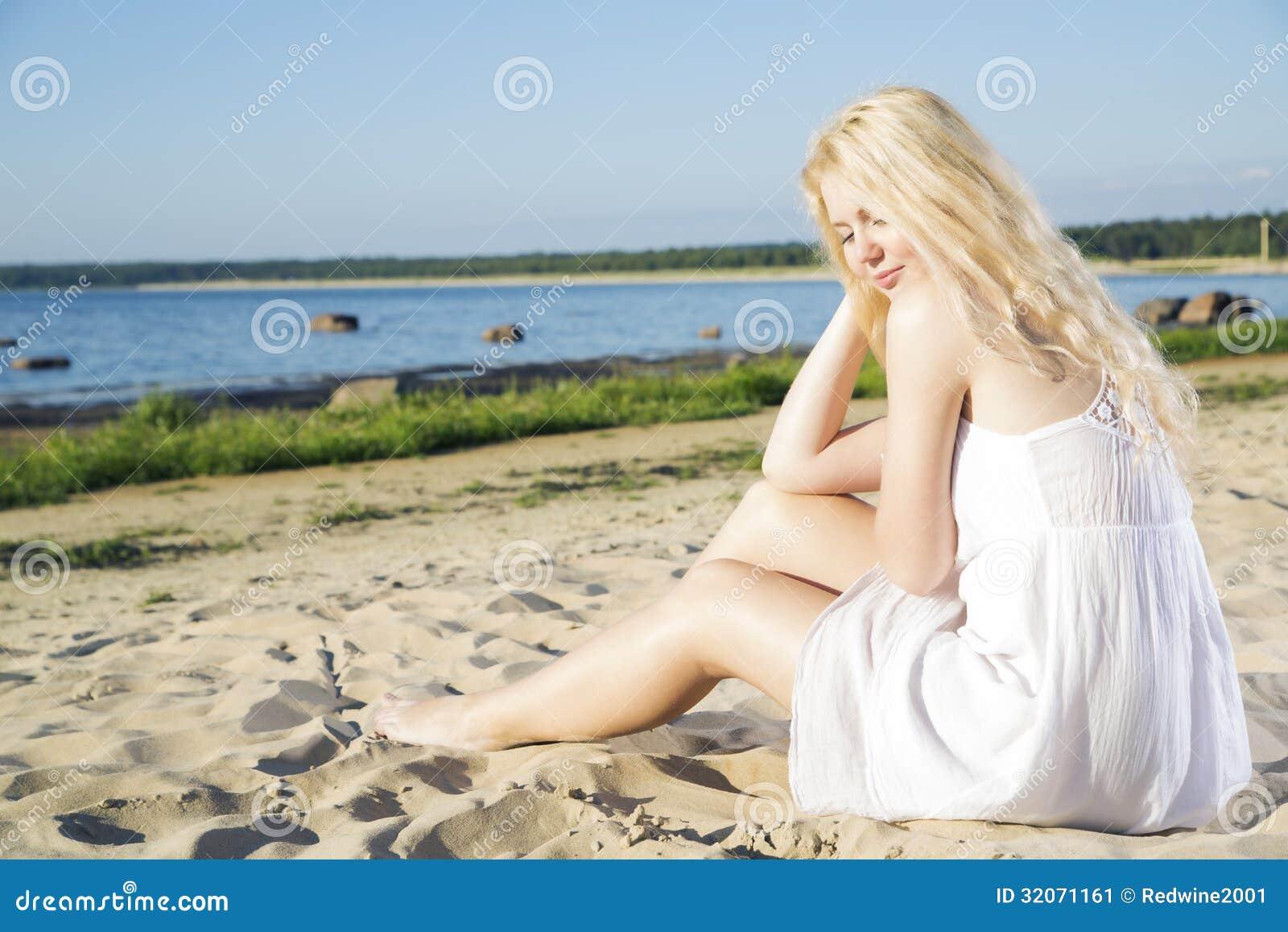 Femme dans l indulgence blanche de robe sur la plage