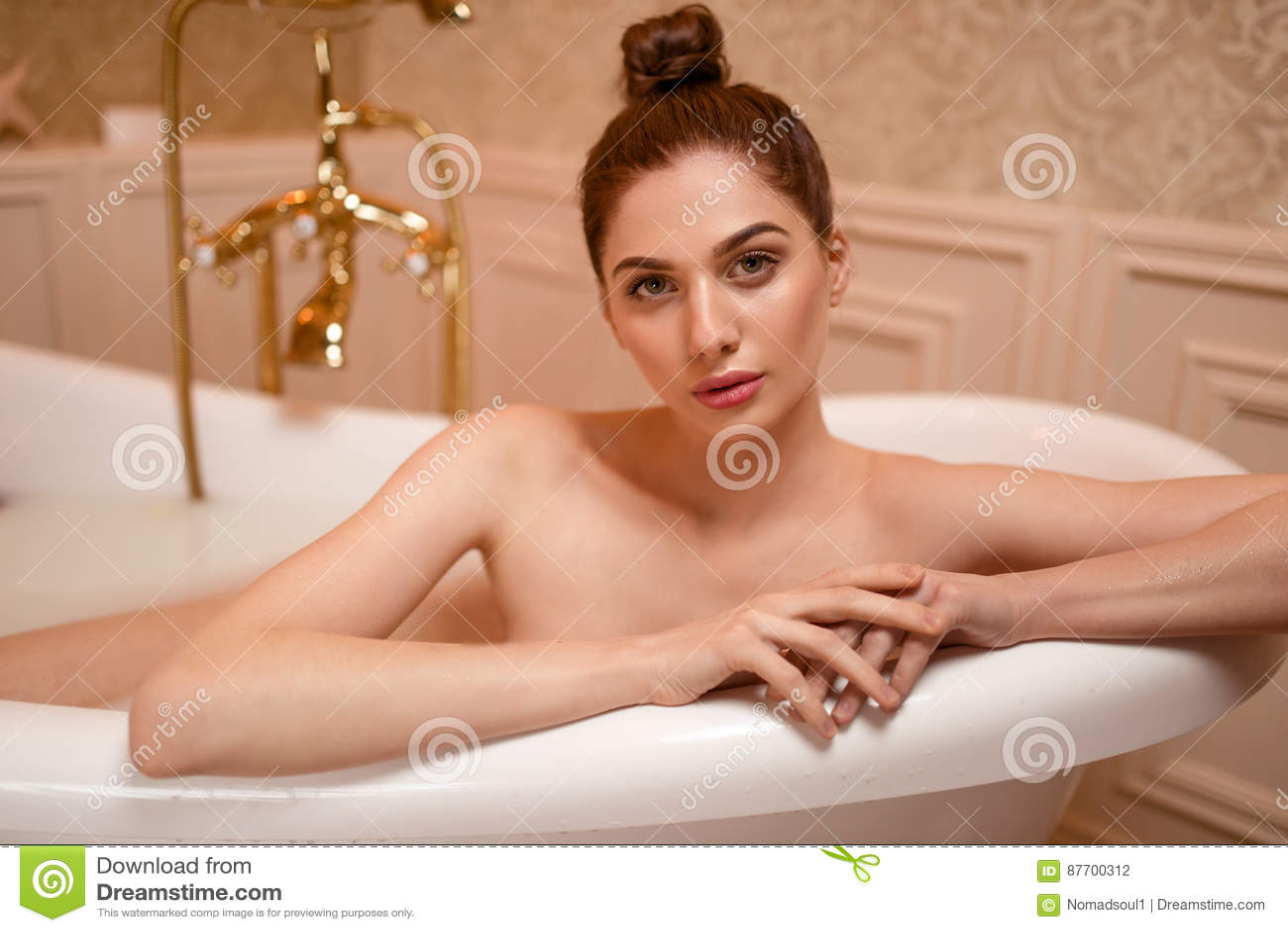 Femme dans la baignoire avec les pétales de rose et la mousse