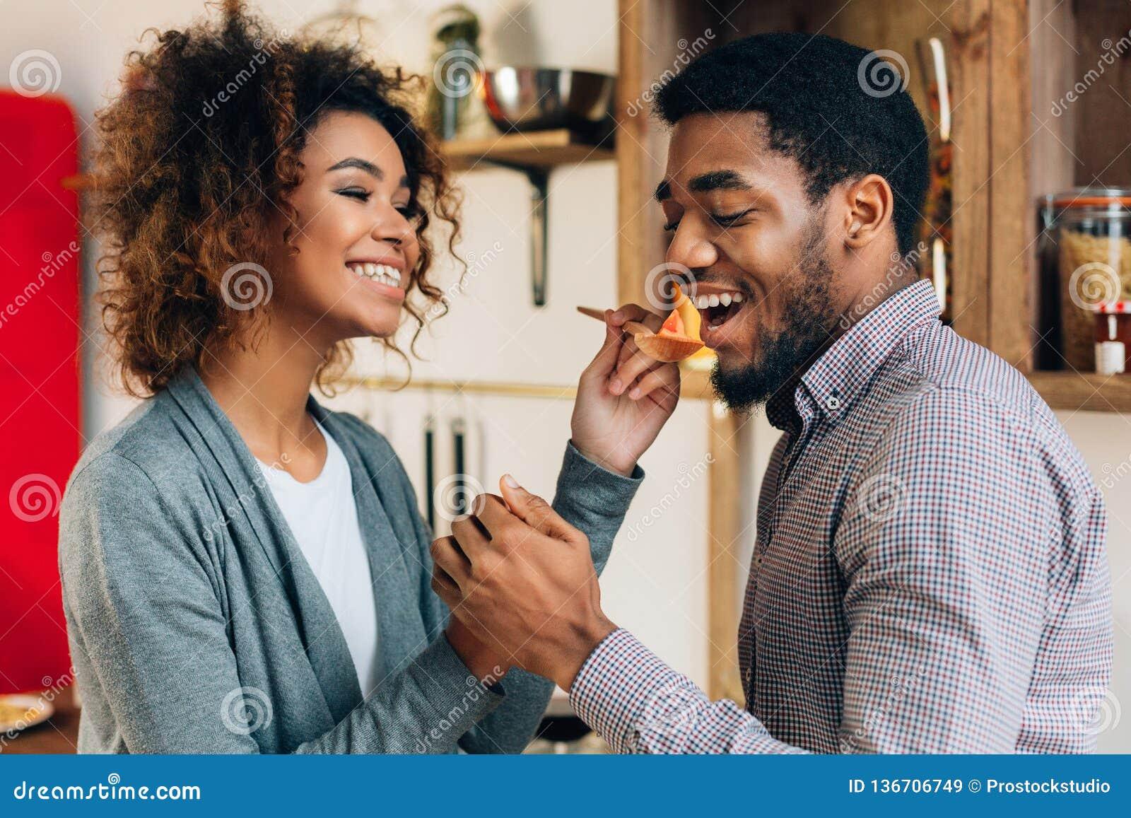 Femme dans la cuisine laissant le repas de goût d homme avec la cuillère en bois