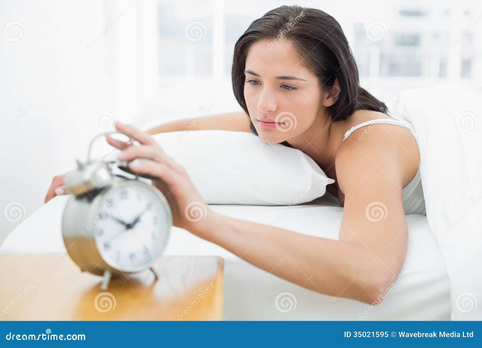 Femme Au Reveil femme dans la main de élargissement de lit au réveil image stock