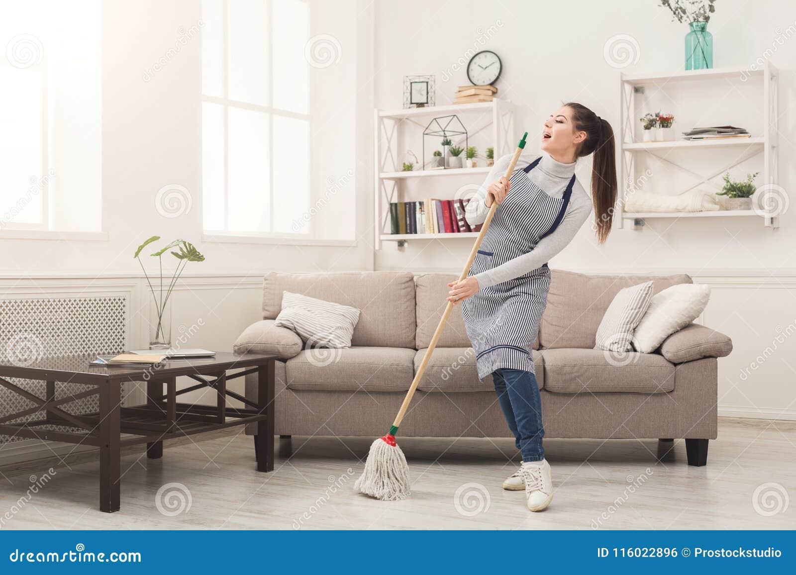 Femme dans la maison uniforme de nettoyage avec le balai et l amusement de avoir