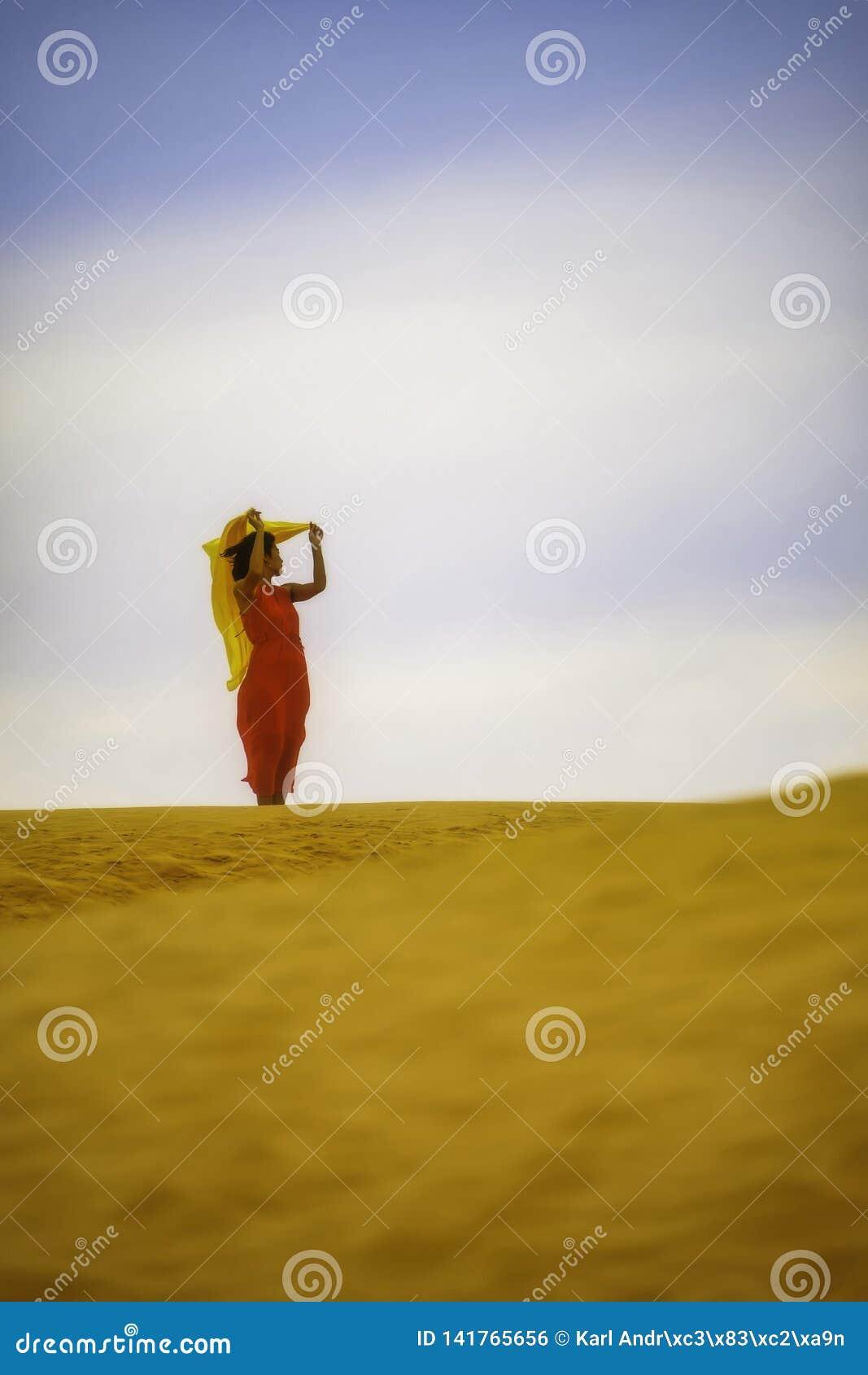 Femme dans la position rouge de robe dans le désert