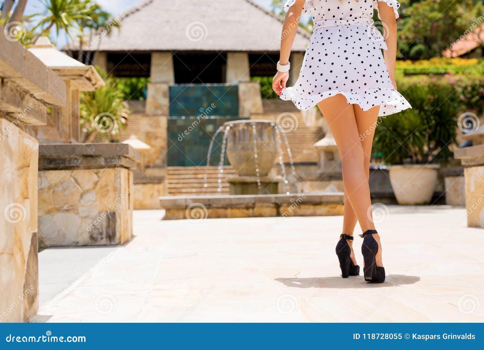 Femme dans la robe blanche et des talons noirs