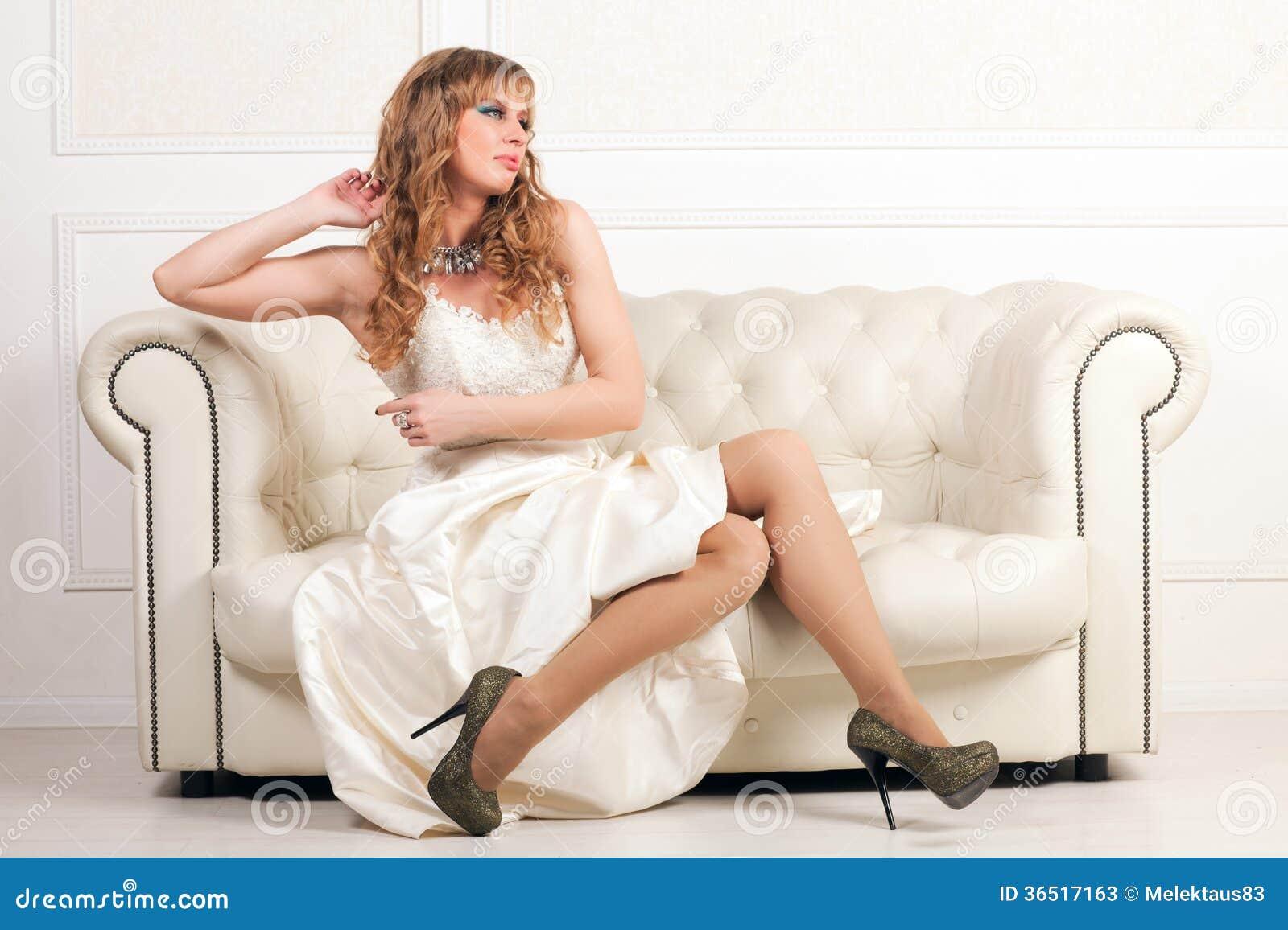 Femme dans la robe blanche se reposant sur un sofa