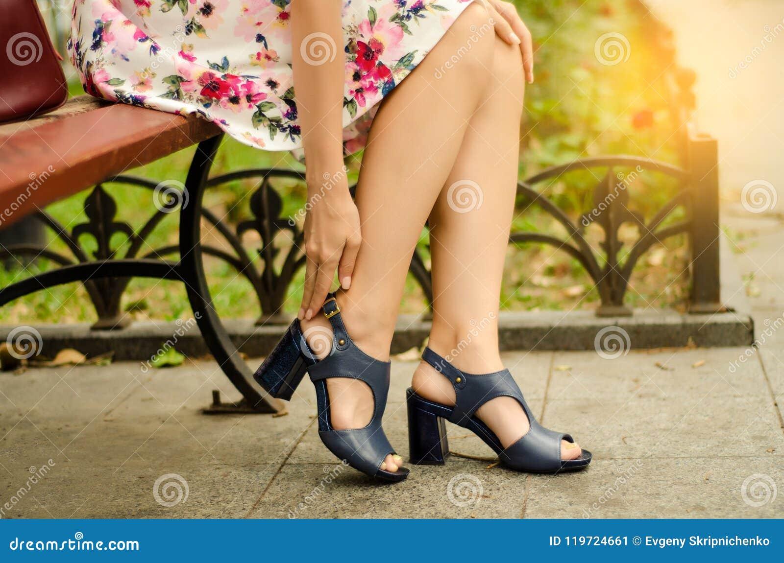 Femme dans la robe du pied dans les chaussures de la douleur de rue de banc dans les jambes