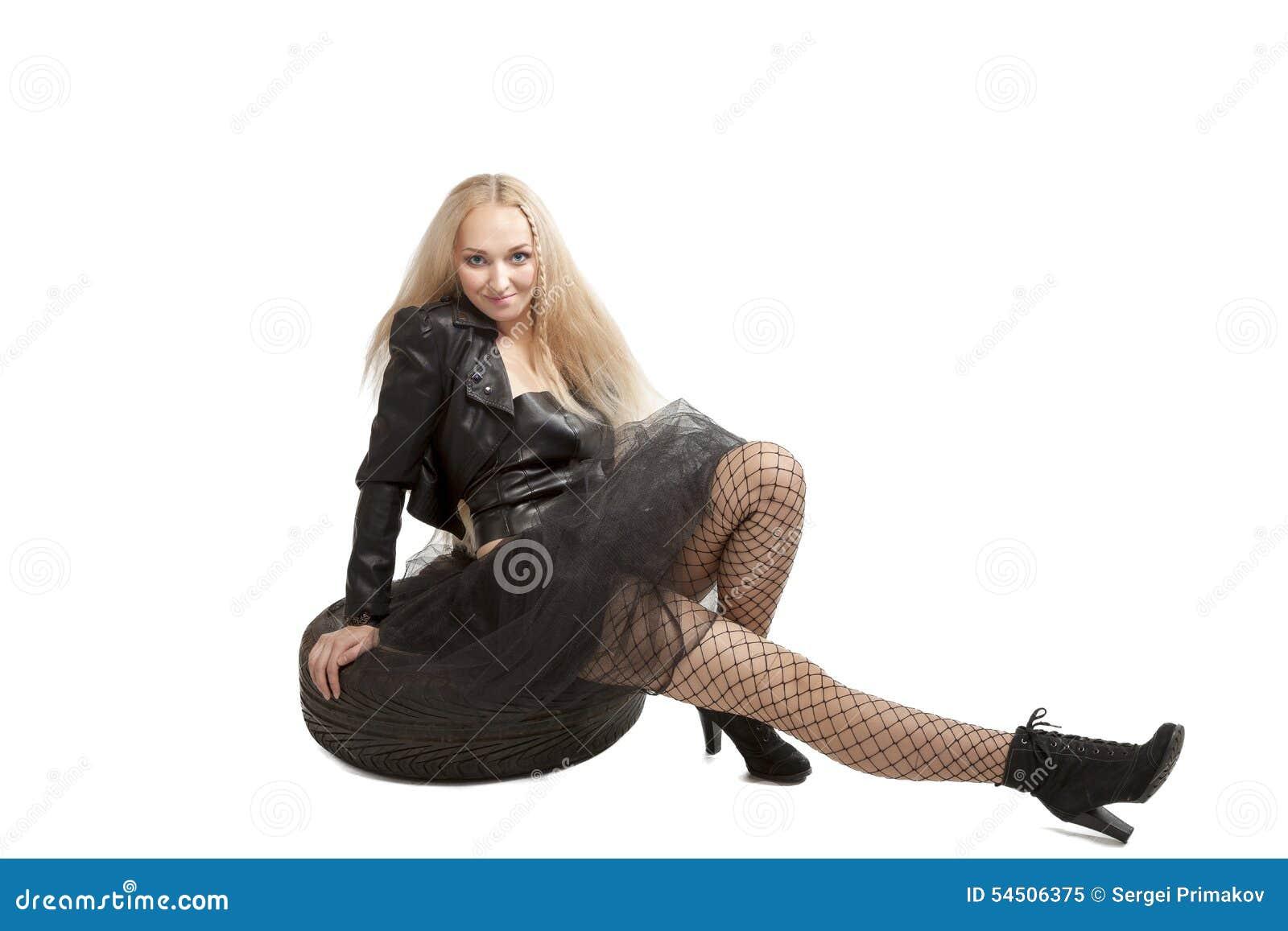 Femme dans la robe noire avec le pneu de voiture