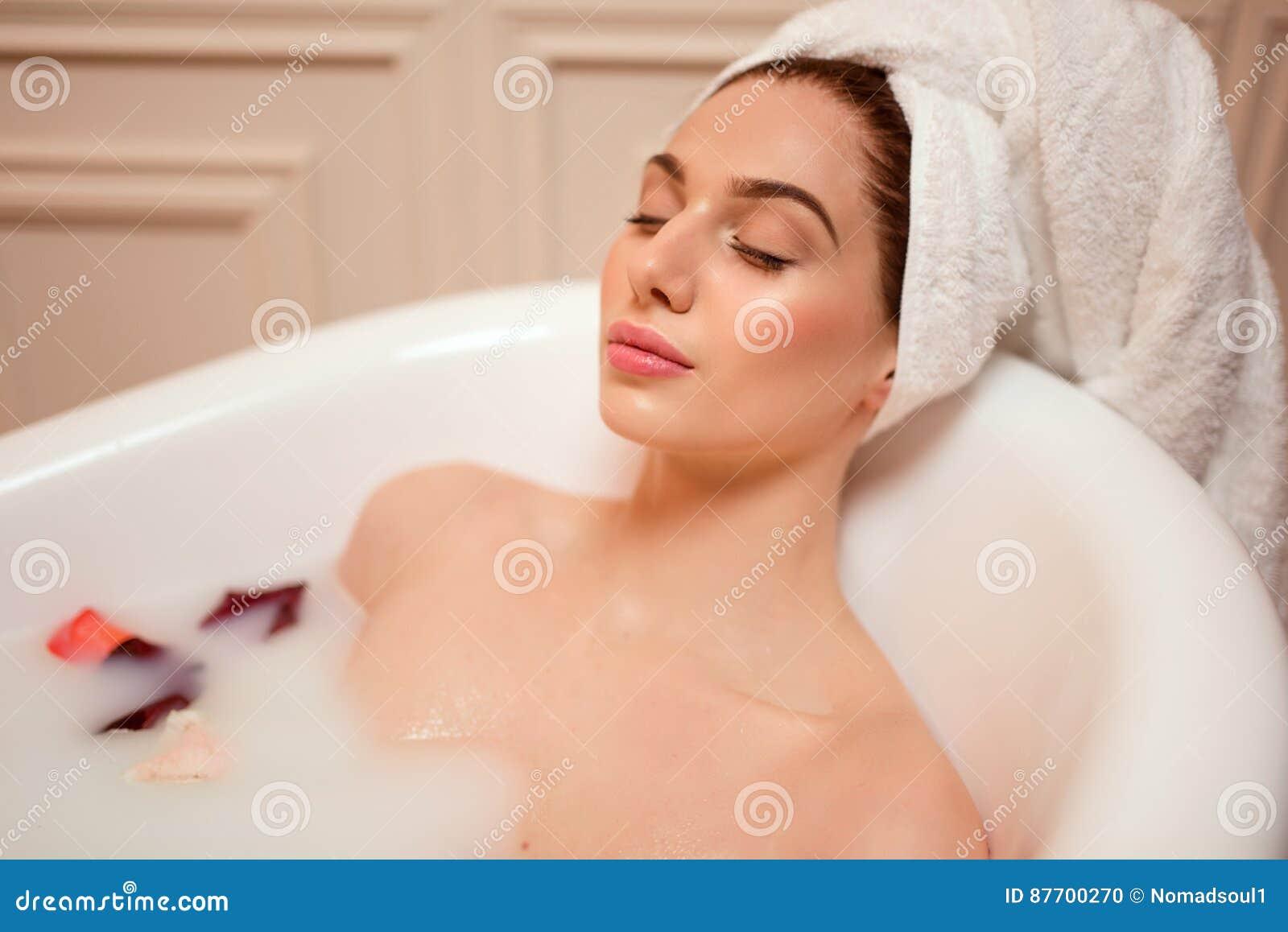 Femme dans la salle de bains avec des pétales de rose