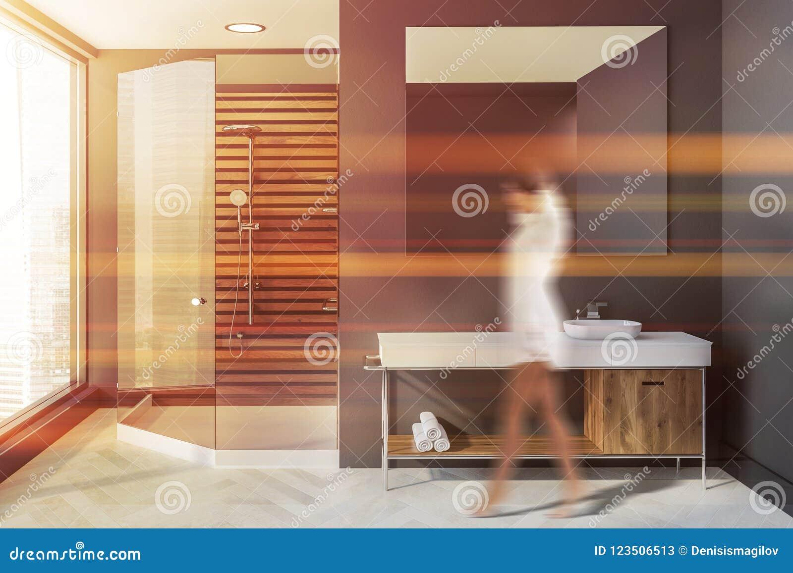Femme dans la salle de bains scandinave grise, évier, douche
