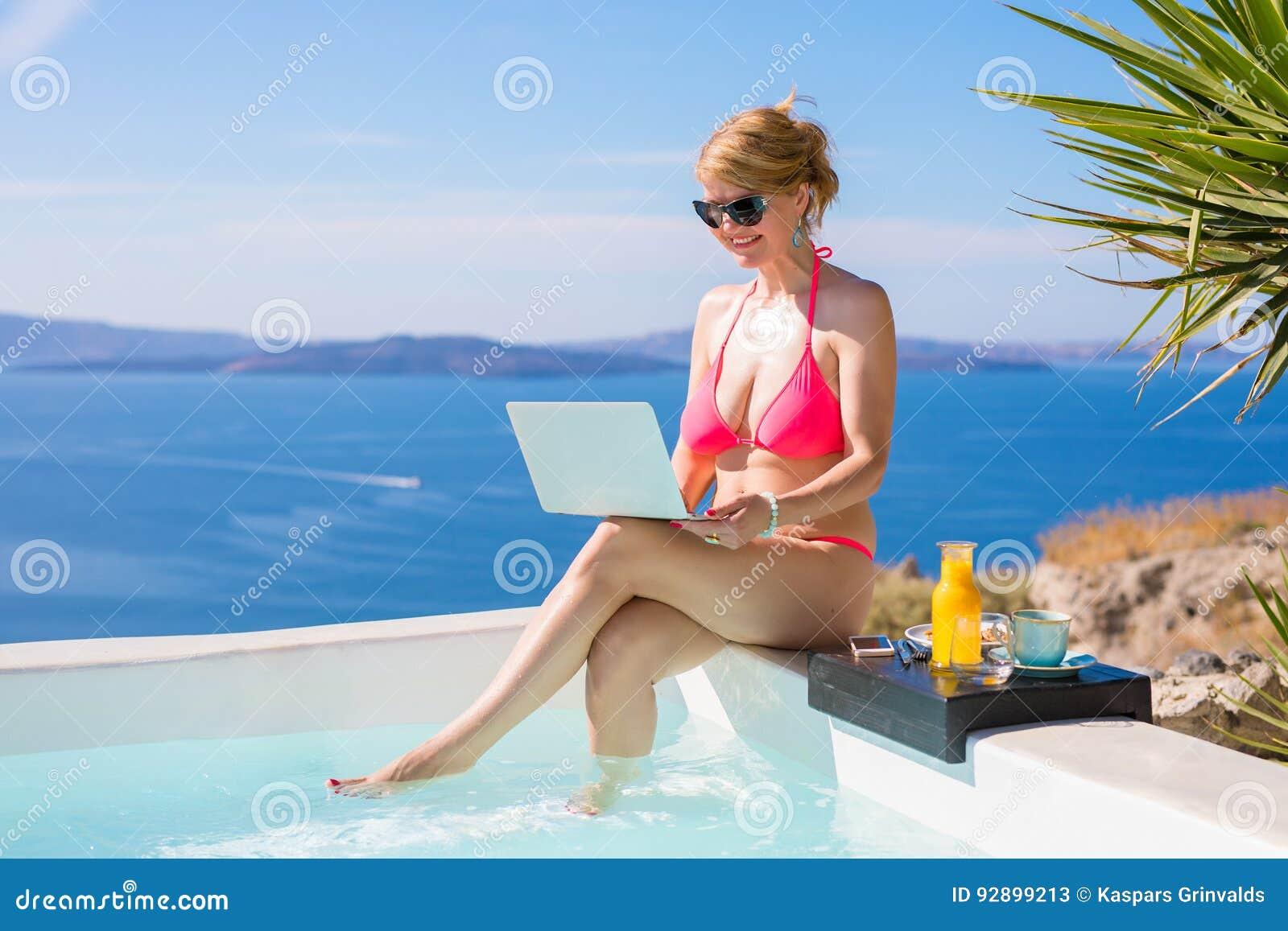 Femme dans le bikini fonctionnant avec l ordinateur portable à côté de la piscine