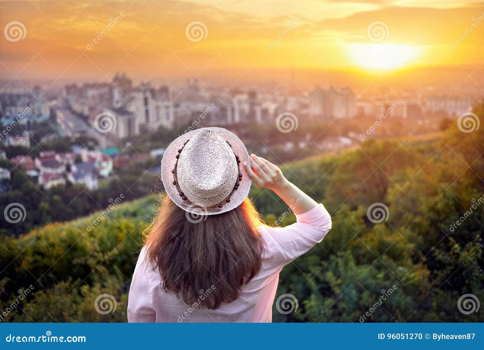 Femme dans le chapeau à la vue de ville de coucher du soleil