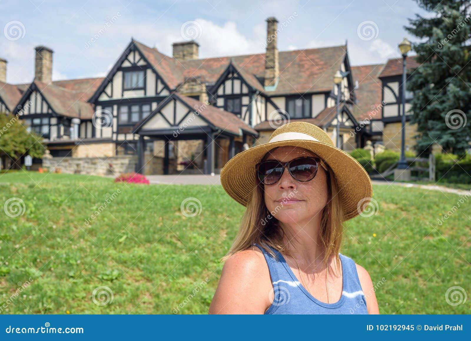 Femme dans le chapeau de soleil se reposant devant le manoir de style de tudor